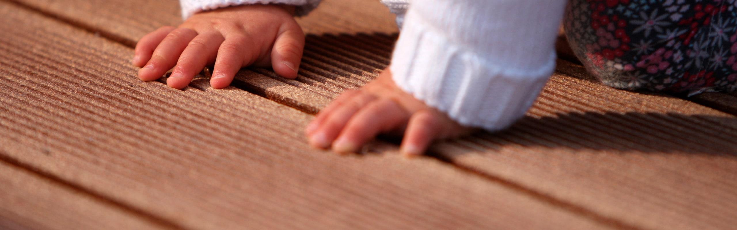 Baby Hände auf Holzfussboden von Holz Heck