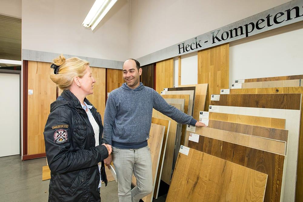 Holz Heck Mitarbeiter berät Kundin zu verschiedenen Bodenbelägen